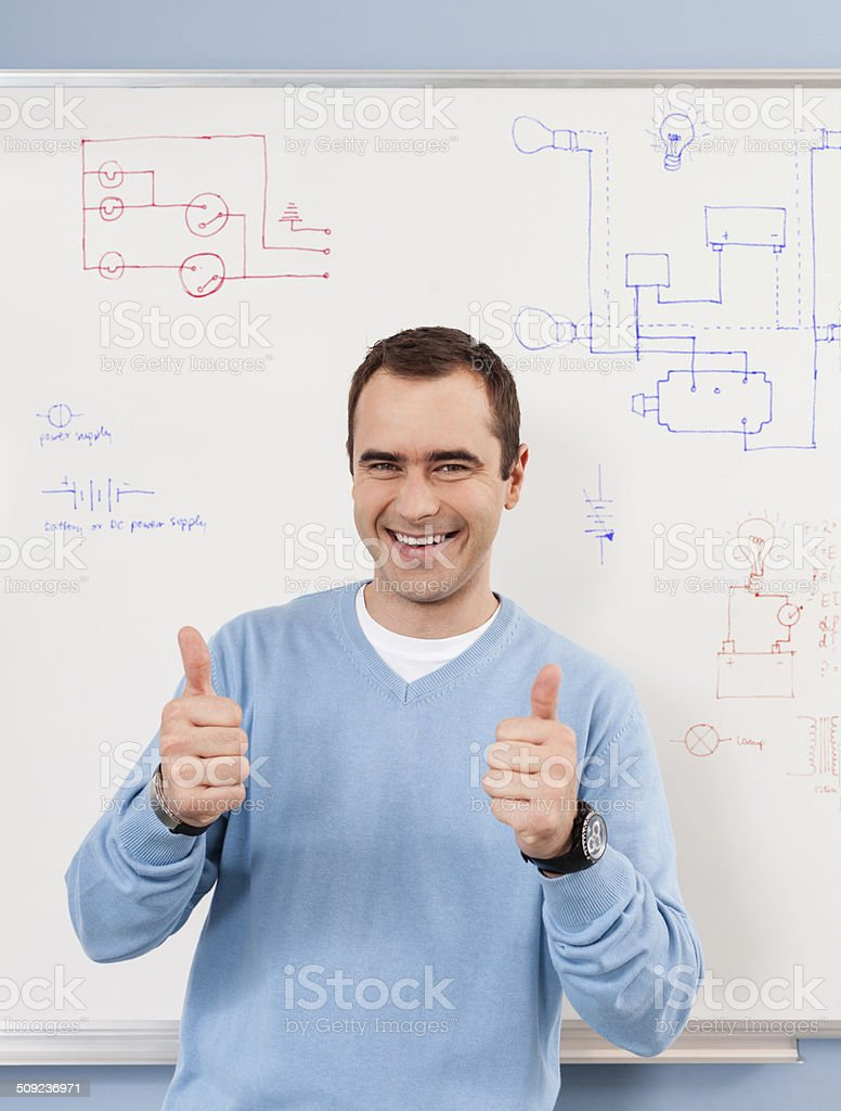 Cheerful Teacher Portrait of happy male teacher standing against whiteboard with thumbs up. 30-39 Years Stock Photo