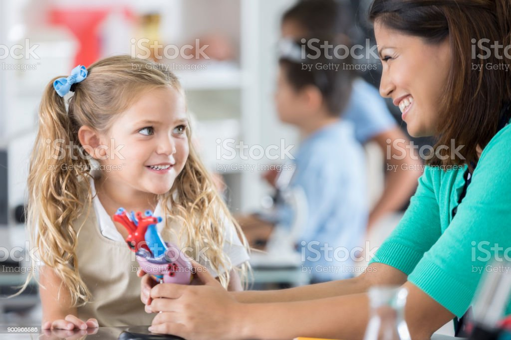Happy mid adult Asian school teacher talks with young girl about the...