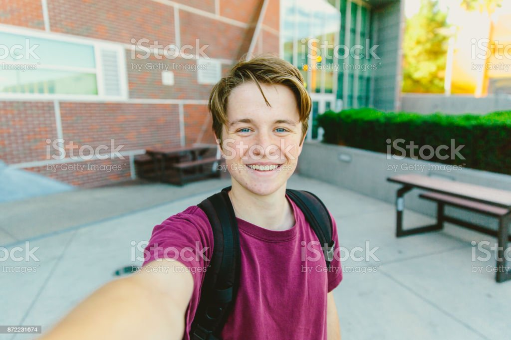 Cheerful Teen Boy With Backpack Taking Selfie Outside stock photo