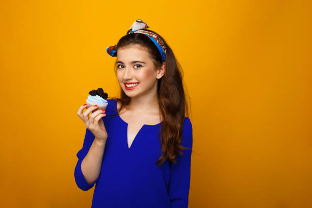 fröhliche teenager-mädchen in bunten kleidern, in der hand einen kuchen, blick auf die kamera, über gelben hintergrund. kopieren sie den speicherplatz. - make up torte stock-fotos und bilder