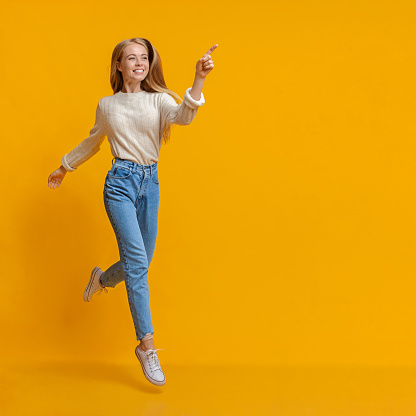istock Cheerful teen girl jumping and pointing aside on orange background 1179968090