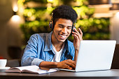 Cheerful black young guy with headset looking at laptop, having fun while studying, cafe interior