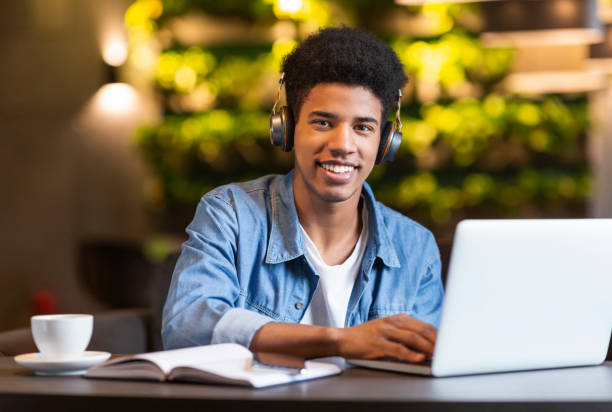 Cheerful teen guy with headset working with laptop stock photo