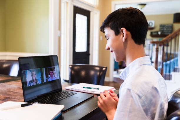 Cheerful teenage boy talks with teacher via video call While distance learning during the COVID-19 pandemic, a teenage boy talks with a female teacher via video call. The boy is using a laptop to communicate with the teacher. middle school teacher stock pictures, royalty-free photos & images