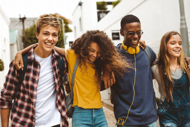 Cheerful teenage friends enjoying outdoors Teenage boys and girls walking in the street holding each other. Smiling college friends walking together in street wearing college bags having fun. jacoblund stock pictures, royalty-free photos & images