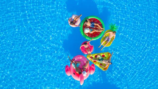 antenne: fröhliche teenage freunden volleyball zu spielen spaß floaties im pool - kinderparty spiele stock-fotos und bilder