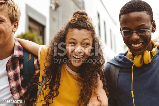 Close up of a smiling teenage girl standing outdoors with college friends. Group of multiethnic boys and a girl having fun standing outdoors with arms around each other.