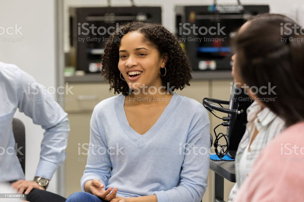 Cute teenage girl smiles as she talks with her friends and teacher...