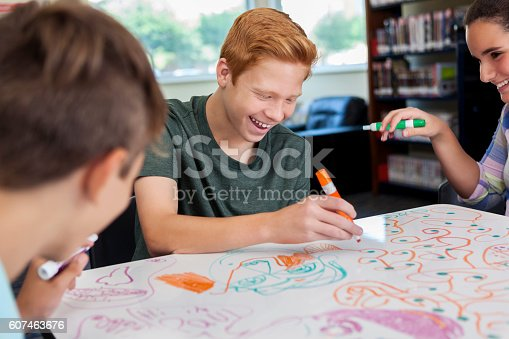 istock Cheerful teenagers drawing together at local makerspace 607463676