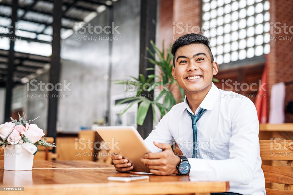 Cheerful Thai entrepreneur holding digital tablet stock photo