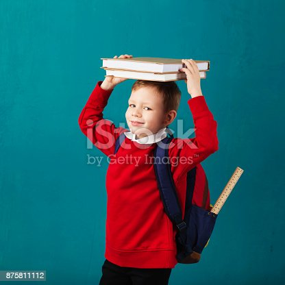 istock Cheerful thoughtful little school boy in school uniform with backpack and big pile of books standing against blue wall. Looking at camera. School concept. Back to School 875811112