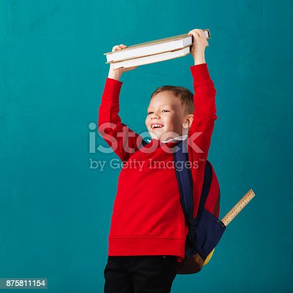 istock Cheerful thoughtful little school boy in school uniform with backpack and big pile of books standing against blue wall. Looking at camera. School concept. Back to School 875811154