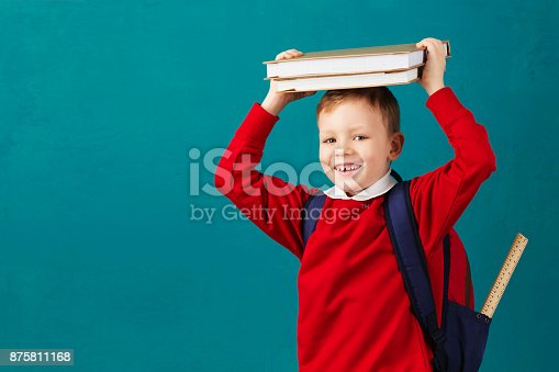 istock Cheerful thoughtful little school boy in school uniform with backpack and big pile of books standing against blue wall. Looking at camera. School concept. Back to School 875811168