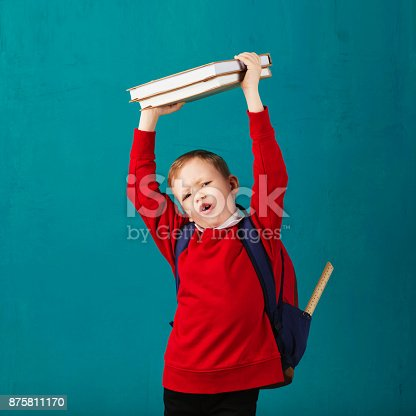 istock Cheerful thoughtful little school boy in school uniform with backpack and big pile of books standing against blue wall. Looking at camera. School concept. Back to School 875811170