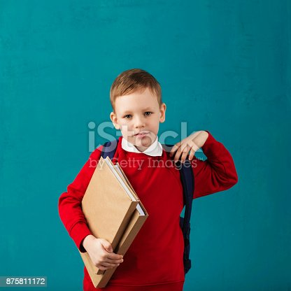istock Cheerful thoughtful little school boy in school uniform with backpack and big pile of books standing against blue wall. Looking at camera. School concept. Back to School 875811172