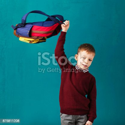 istock Cheerful thoughtful little school boy in school uniform with backpack and big pile of books standing against blue wall. Looking at camera. School concept. Back to School 875811208