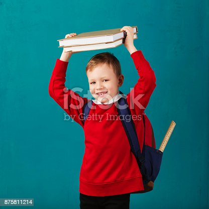 istock Cheerful thoughtful little school boy in school uniform with backpack and big pile of books standing against blue wall. Looking at camera. School concept. Back to School 875811214