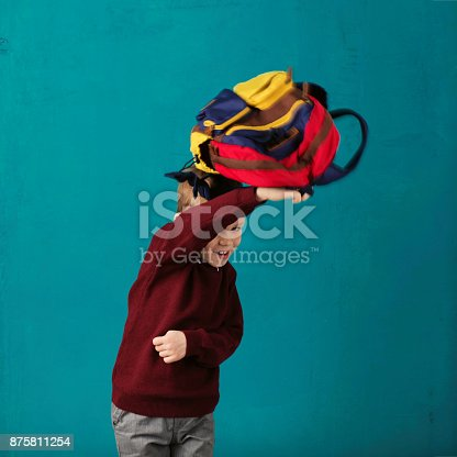 istock Cheerful thoughtful little school boy in school uniform with backpack and big pile of books standing against blue wall. Looking at camera. School concept. Back to School 875811254