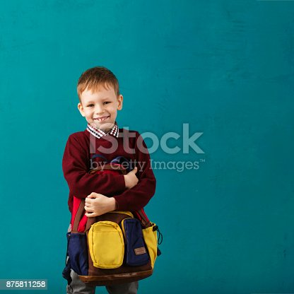 istock Cheerful thoughtful little school boy in school uniform with backpack and big pile of books standing against blue wall. Looking at camera. School concept. Back to School 875811258