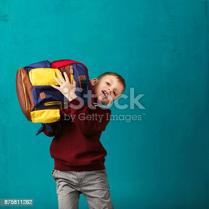 istock Cheerful thoughtful little school boy in school uniform with backpack and big pile of books standing against blue wall. Looking at camera. School concept. Back to School 875811262