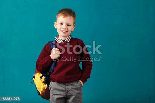 istock Cheerful thoughtful little school boy in school uniform with backpack and big pile of books standing against blue wall. Looking at camera. School concept. Back to School 875811278