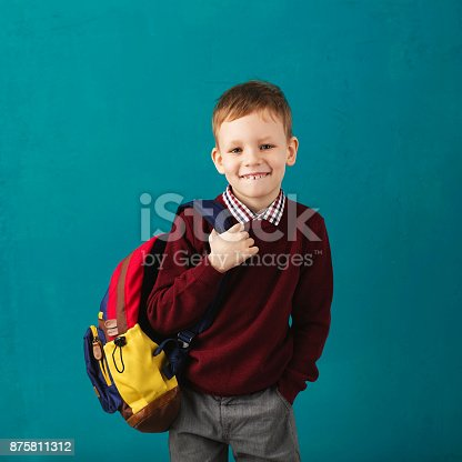 istock Cheerful thoughtful little school boy in school uniform with backpack and big pile of books standing against blue wall. Looking at camera. School concept. Back to School 875811312