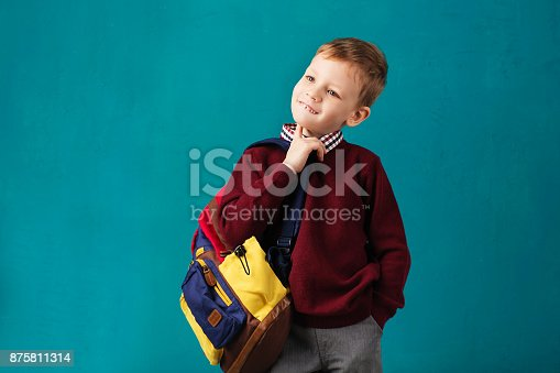 istock Cheerful thoughtful little school boy in school uniform with backpack and big pile of books standing against blue wall. Looking at camera. School concept. Back to School 875811314