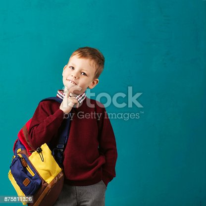 istock Cheerful thoughtful little school boy in school uniform with backpack and big pile of books standing against blue wall. Looking at camera. School concept. Back to School 875811326