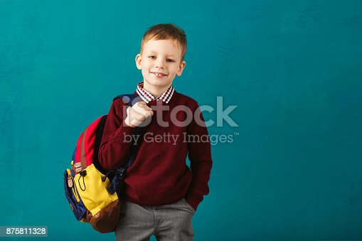 istock Cheerful thoughtful little school boy in school uniform with backpack and big pile of books standing against blue wall. Looking at camera. School concept. Back to School 875811328