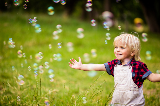 Cheerful toddler boy playing with soap bubbles in park