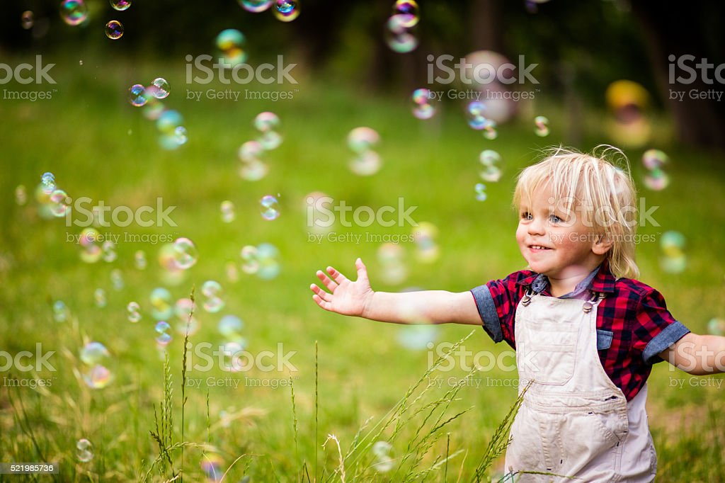 Cheerful toddler boy playing with soap bubbles in park stock photo
