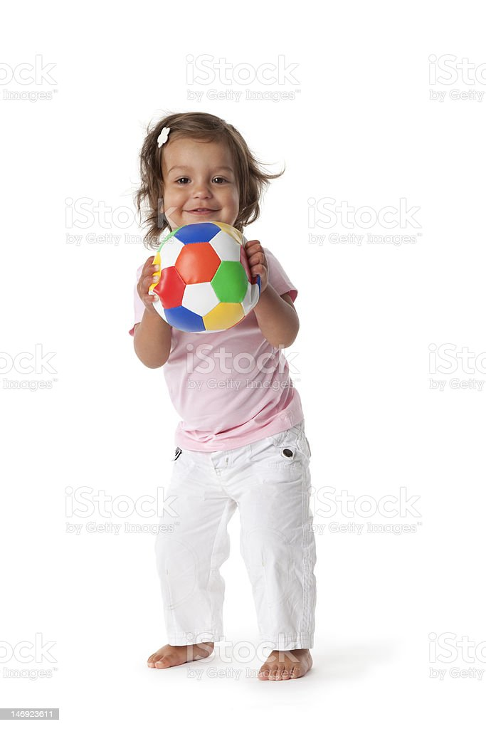 Cheerful toddler girl playing with a colored ball stock photo
