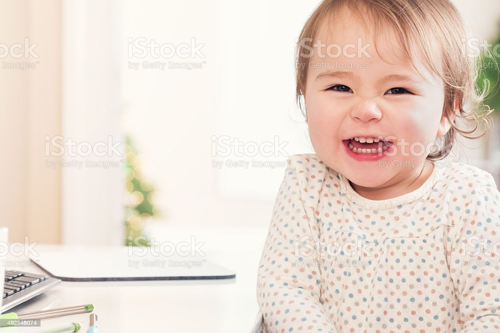 Cheerful toddler girl with a huge smile stock photo