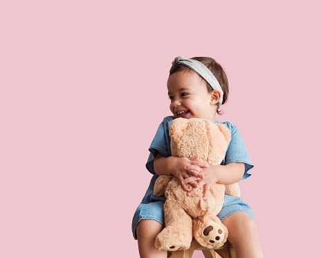 A little girl hugging her teddy bear with both hands and smiling as she looks away from the camera.