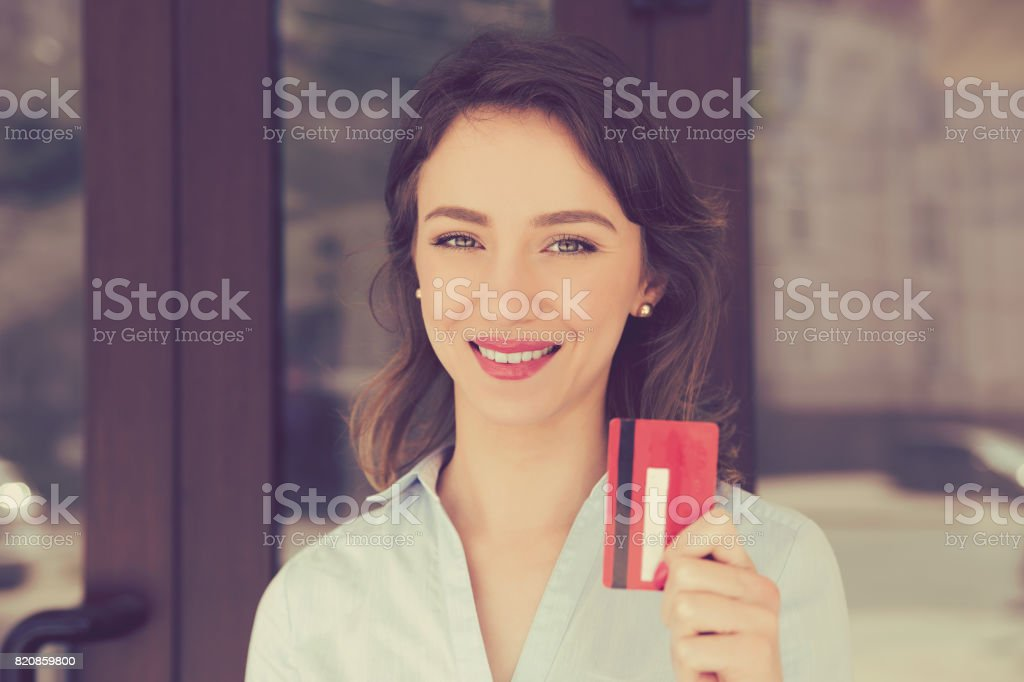 Cheerful toothy smile woman holding showing loyalty card near store shopping mall outdoors in street. Shopaholic concept pay with credit card banking stock photo