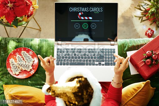 Holiday season. Upper view of cheerful trendy female in sparkle gold sequin santa hat sitting on sofa in the modern living room at Christmas listening to the music on a laptop.