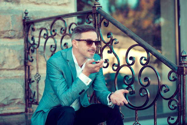 Cheerful trendy man leaving voice message stock photo