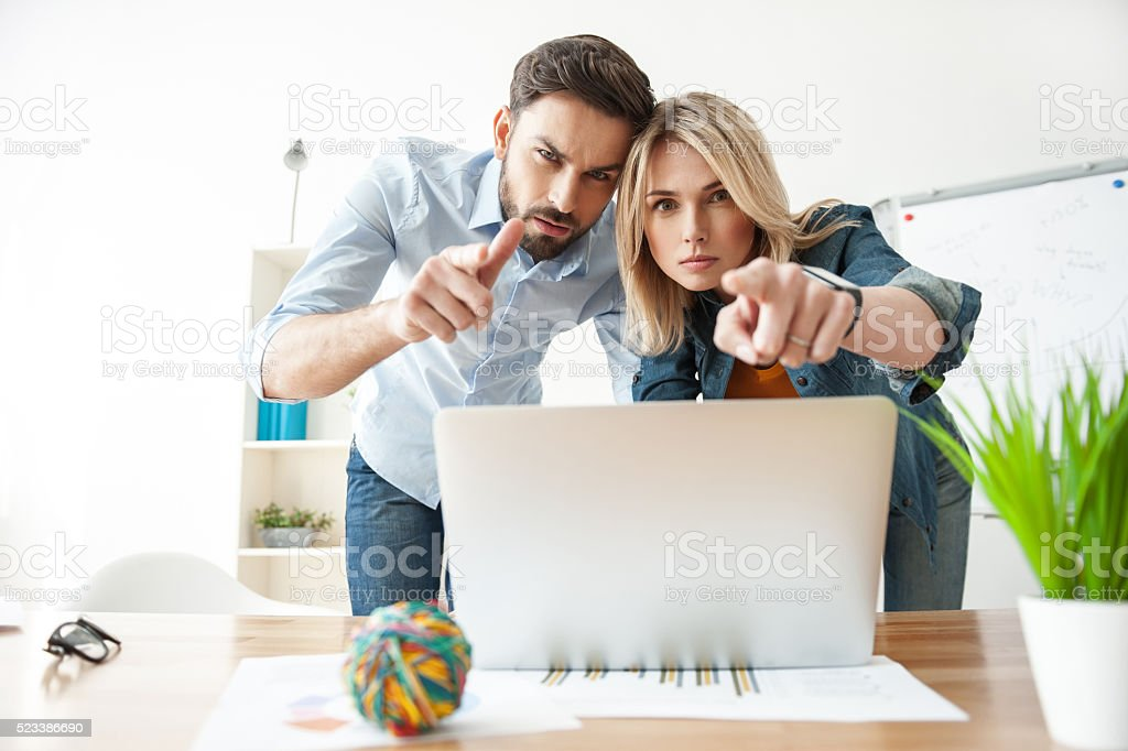 Cheerful two colleagues are relating to work with seriousness stock photo