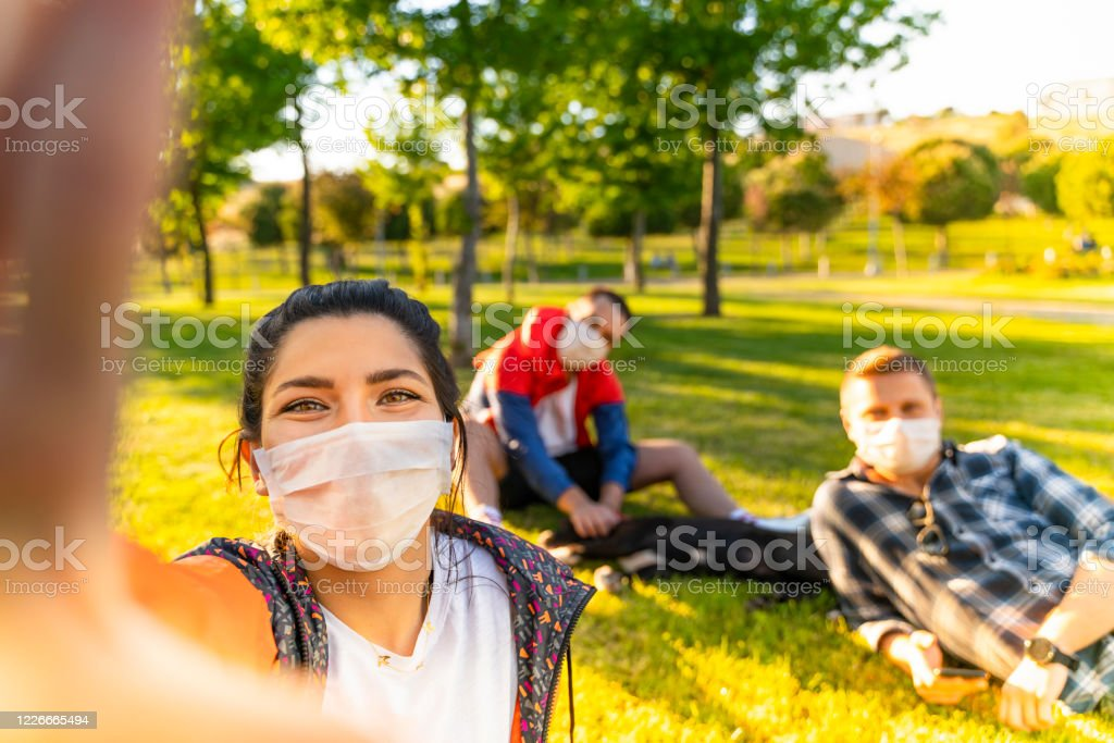 Cheerful university student taking selfie with friends sitting on grass Cheerful university student taking selfie with friends sitting on grass Adult Stock Photo
