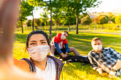 Cheerful university student taking selfie with friends sitting on grass