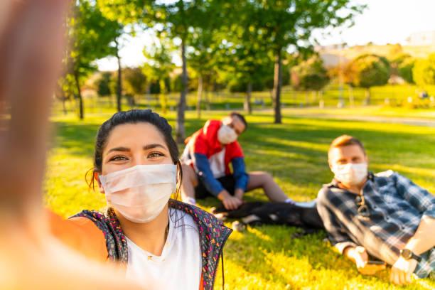 wesoły student biorąc selfie z przyjaciółmi siedzącymi na trawie - wypoczynek zdjęcia i obrazy z banku zdjęć