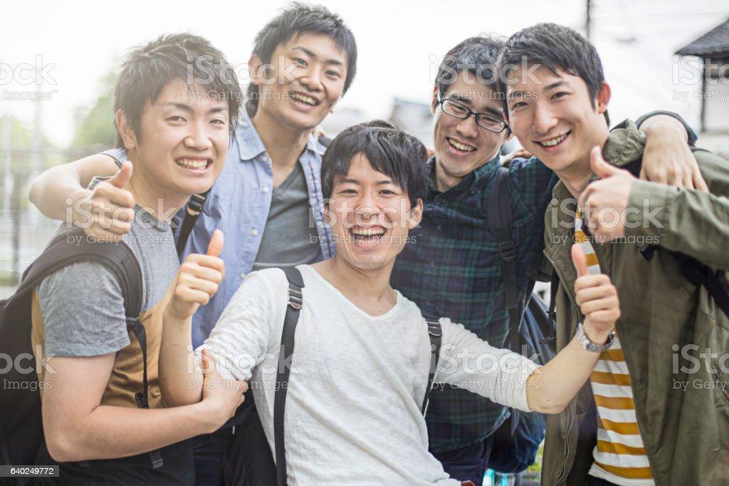 Cheerful university students gesturing thumbs up ストックフォト