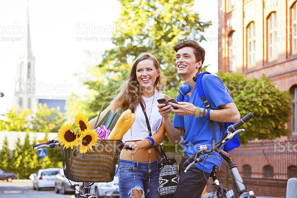 Cheerful urban young couple Outdoor portrait of urban young couple standing on the street with blicycles, a guy holding cell phones in hands. 20-24 Years Stock Photo