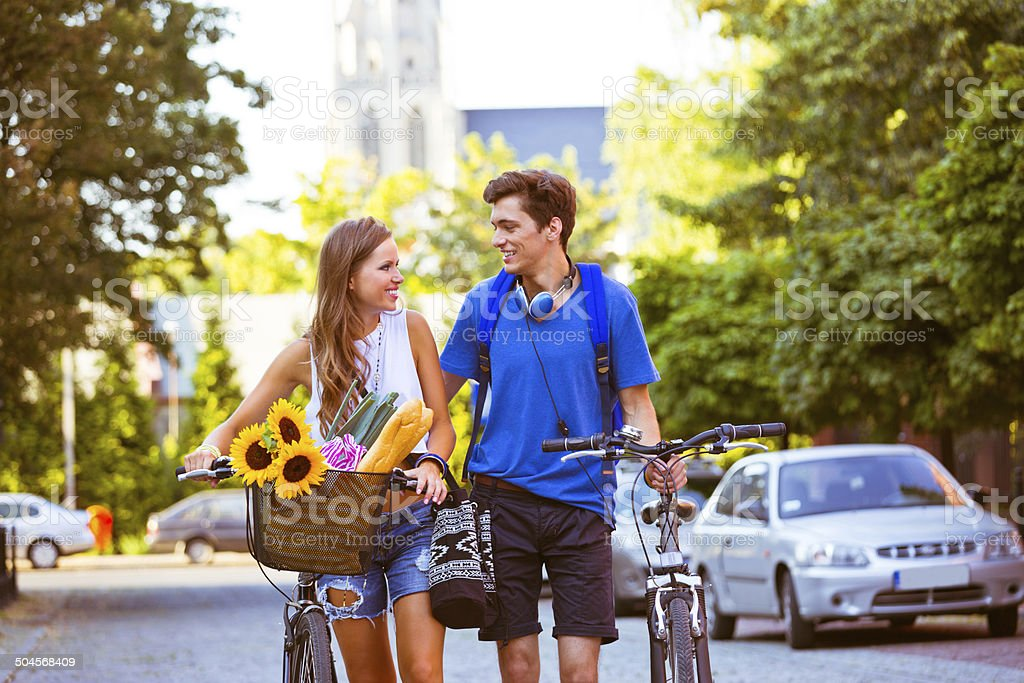 Cheerful urban young couple Outdoor portrait of urban young couple walking the street with blicycles and talking. 20-24 Years Stock Photo
