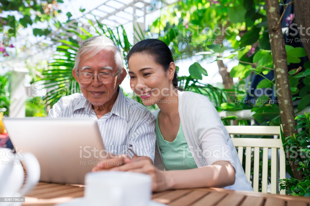 Cheerful Vietnamese father and daughter sitting in outdoor cafe and watching something on tablet computer stock photo
