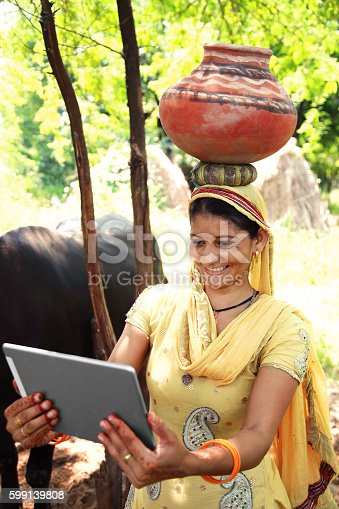 Cheerful confident happy young women of Indian ethnicity carrying clay pot on her head and holding digital tablet outdoor nature.
