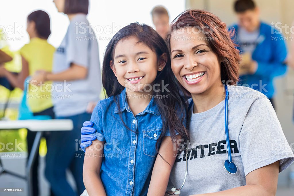 Cheerful volunteer and young girl smiling and embracing stock photo