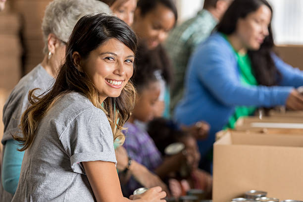 Cheerful volunteer packs boxes at food drive stock photo