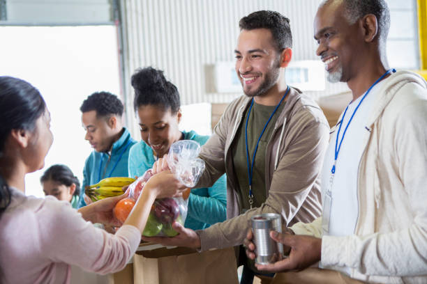 cheerful volunteers receive donations during food drive - volunteer stock photos and pictures