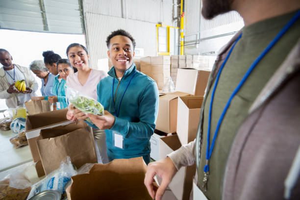 Cheerful volunteers working in food bank stock photo